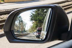 Side view mirror in modern car with view of street with parked c Royalty Free Stock Photos