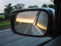 Side view mirror reflection of the two-lane winding road. Royalty Free Stock Photos