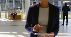 Mixed-race businessman phoning in the lobby at office 4k. Side view of a mixed-race businessman walking in office lobby while talking to his mobile phone 4k stock video footage