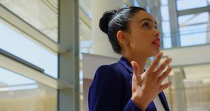 Mixed-race businesswoman practicing speech in the office 4k. Side view of a mixed-race businesswoman holding her script and practicing her speech in the office stock footage