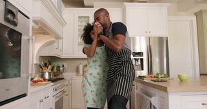 Happy mixed race couple cooking and dancing in their kitchen