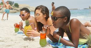 Side view of mixed-race female friends drinking cocktail drinks on the beach 4k stock footage