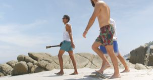 Side view of mixed race male friends carrying ice box on the beach 4k stock video