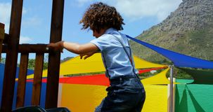 Side view of mixed-race schoolgirl playing in school playground on a sunny day 4k. Side view of mixed-race schoolgirl playing in school playground on a sunny day stock footage