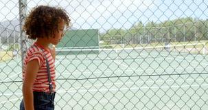 Side view of mixed-race schoolgirl walking near wire mesh fence at school 4k. Side view of mixed-race schoolgirl walking near wire mesh fence at school. Tennis stock footage