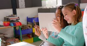 Side view of mixed-race schoolgirls studying on digital tablet in the classroom 4k. Side view of mixed-race schoolgirls studying on digital tablet in the stock footage