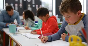 Side view of Mixed-race schoolkids drawing in the classroom 4k. Side view of Mixed-race schoolkids drawing in the classroom. Male teacher teaching schoolgirl in stock video footage