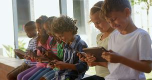 Side view of mixed-race schoolkids using digital tablet in the corridor 4k. Side view of mixed-race schoolkids using digital tablet in the corridor. They are stock footage