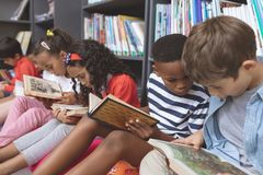 School kids sitting on cushions and studying over books in a library. Side view of mixte ethnicity school kids sitting on cushions and studying over books in a royalty free stock image