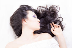 Side view of model portrait with black hair over white Royalty Free Stock Images