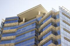Side view of a modern corporate building with a terrace. Its facade is mainly glass windows and cream yellowish tiles. Low angle shot. San Pedro, Nuevo Leon stock photo