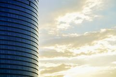 Side view of the modern glass skyscraper facade on the late sunrise sky background. Side view of the modern skyscraper facade on the late sunrise sky background Stock Photos