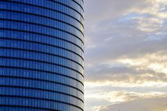 Side view of the modern glass skyscraper facade on the late sunrise sky background. Side view of the modern skyscraper facade on the late sunrise sky background Stock Image