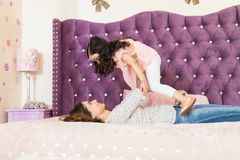 Parent Having Fun With Daughter On Bed stock photo