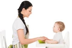 Side view of mother holding hands of baby boy in highchair. Isolated on white background stock photos