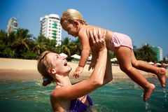 Side-view mother in sea laughs holds in arms small daughter Stock Photo