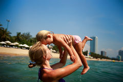 Side-view mother in sea laughs holds in arms small daughter Stock Images