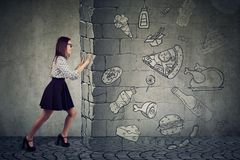 Motivated woman resisting temptation of eating fast foot and choosing better diet. Side view of a motivated young woman resisting temptation of eating fast foot stock photography