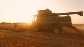 Side view of moving combine. Commercial grain farming royalty free stock photography