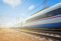 Side view of the moving ultra high speed train runs on rail way with railway infrustructure in the blurred background with flare e. Ffect. Electric high speed royalty free stock photo