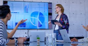 Multi-ethnic business people discussing over chart on screen in modern office 4k. Side view of multi-ethnic business people discussing over chart on screen in stock footage
