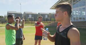 Men drinking water after training on sunny day