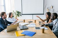 Side view of multicultural business people having business meeting. In office royalty free stock photography
