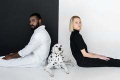 Side view of multicultural couple sitting back to back with dalmatian dog. On floor royalty free stock photo