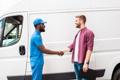 Side view of multicultural courier and client shaking hands. Near van royalty free stock images
