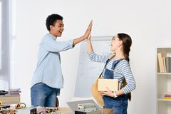 Side view of multicultural friends giving high five. At home royalty free stock photography