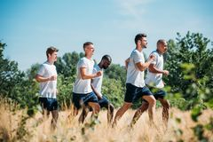 Side view of multicultural group of soldiers running. On range royalty free stock photography