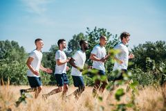 Side view of multicultural group of soldiers running. On range royalty free stock image