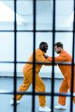 Side view of multicultural prisoners threatening each other behind. Prison bars royalty free stock photos