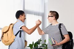 Side view of multicultural teen boys greeting at home royalty free stock images