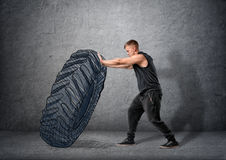 Side view of muscled young man pushing drawn tire to build strength Stock Photography