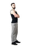 Side view of muscular athlete in tank top with crossed arms looking at camera. Royalty Free Stock Photography