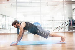 Side view of muscular man doing push up on mat Royalty Free Stock Photo