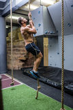 Side view of muscular man doing rope climbing Stock Images