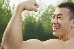 Side view of muscular smiling man showing off and flexing his bicep Royalty Free Stock Photos