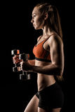 Side view of muscular young woman exercising with dumbbells. Isolated on black Stock Photos