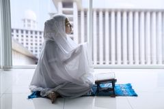 Muslim woman prays to the Allah at home. Side view of Muslim woman praying to the Allah after reading Quran at home with mosque background on the window Royalty Free Stock Photography