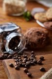 Roasted coffee beans get out of overturned glass jar on homespun tablecloth, selective focus, side view. Side view of natural roasted coffee beans get out of Stock Images