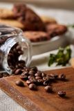 Roasted coffee beans get out of overturned glass jar on homespun tablecloth, selective focus, side view. Side view of natural roasted coffee beans get out of Stock Photography