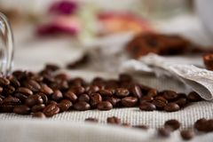 Roasted coffee beans get out of overturned glass jar on homespun tablecloth, selective focus, side view. Side view of natural roasted coffee beans get out of Royalty Free Stock Photo
