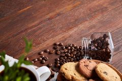 Roasted coffee beans get out of overturned glass jar on homespun tablecloth, selective focus, side view. Side view of natural roasted coffee beans get out of Stock Photos