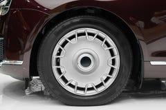 Side view on new luxury car wheel on silver metal rim with black shine tire. Modern classic car wheel stock photo