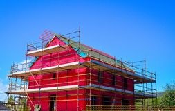 Side view of a new two-storey detached house under construction covered by red protective layer Royalty Free Stock Image