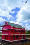 Side view of a new two-storey detached house under construction with red protective layer and scaffolding Stock Images