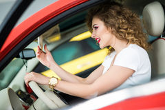 Side view of nice stylish girl touching a rear view mirror and smiling while driving the car. Side view of nice stylish girl touching a rear view mirror Royalty Free Stock Image