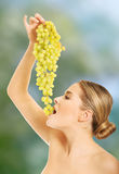 Side view of nude woman eating grapes Stock Photos